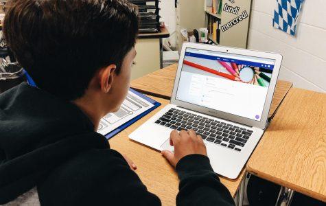 Freshman Caillou Sleiman uses a laptop to check Google Classroom.