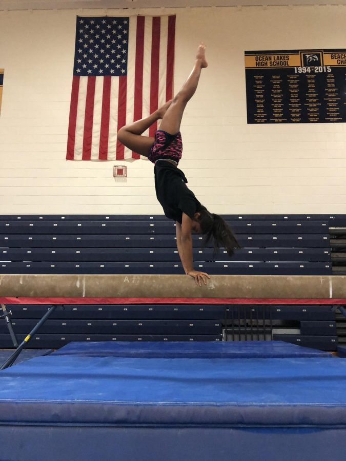 Senior+Rutvi+Patel+performs+a+handstand+on+the+balance+beam+in+the+Ocean+Lakes+gymnasium+on+Nov.+30%2C+2017.