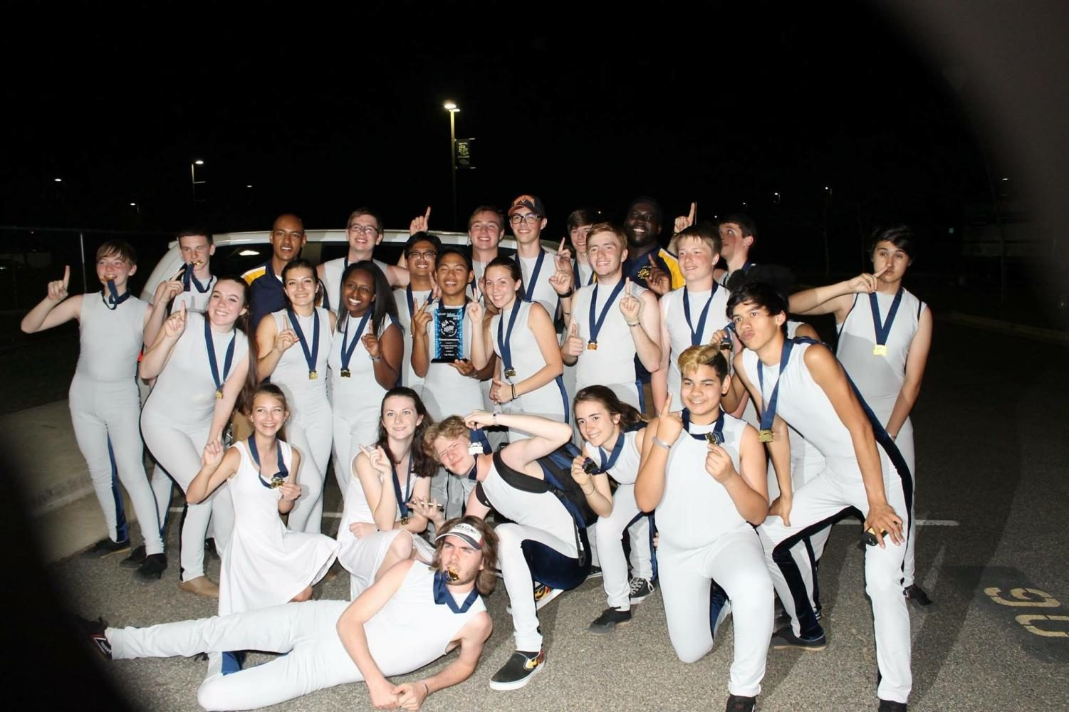 Indoor drumline celebrates their first place win with a trophy and gold medals for all team members in the South County High parking lot.