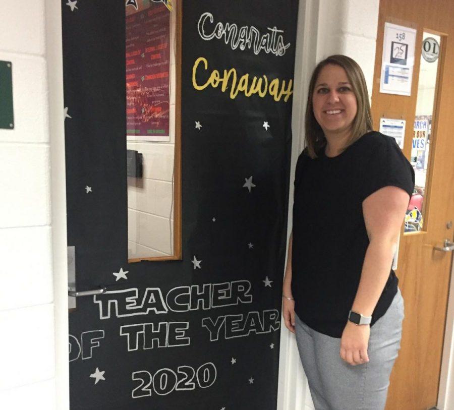 Teacher+of+the+Year%2C+Carlin+Conaway%2C+poses+in+front+of+her+classroom+door+designed+by+SCA.