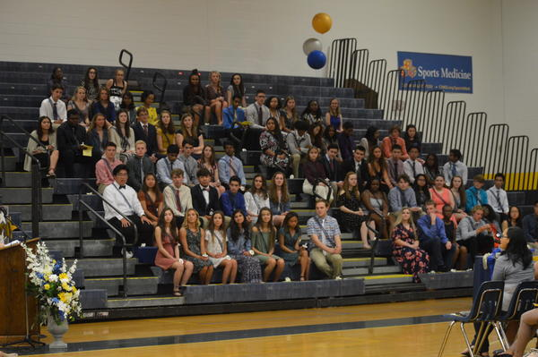 New NHS inductees sit in gymnasium for induction ceremony on April 25.