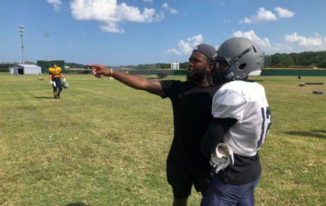 Varsity football recruits alumnus running back coach