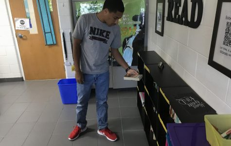 Senior Xavier Adams browses Katie Anderson's catalog of books on Sept. 20, 2019.