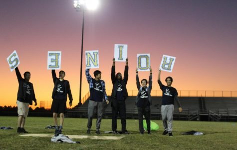 The senior cheerleading team holds up a sign that spells out