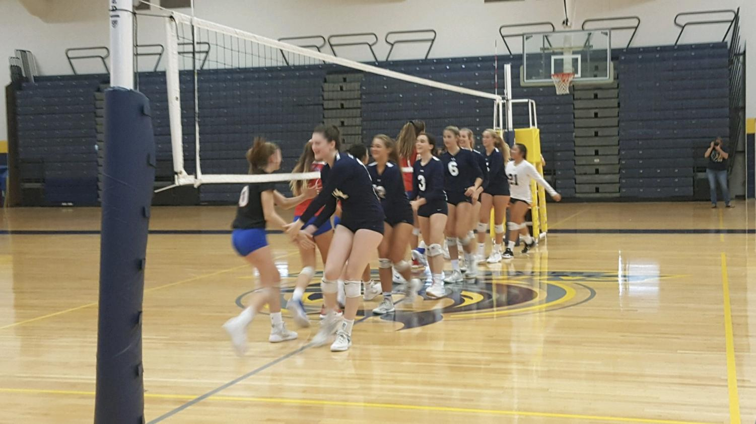 Girls volleyball shakes hands with Princess Anne before a game in the gym on Sept. 25.