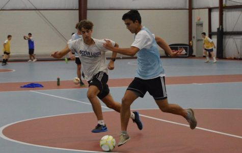 Seniors Matthew Escobar and Jacey McFaddin fight for the ball at the Beach FC indoor facility on Oct. 17.