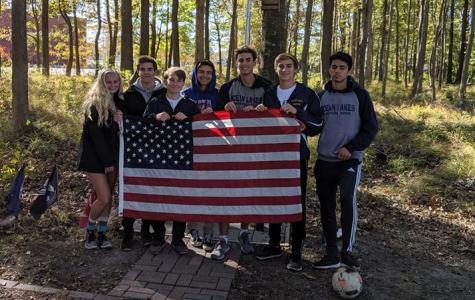 From left: Meredith King, Troy Daigneau, Anthony Crispin, Dakota Gordon, Matt Escobar, Alex Cigurov,  and Yusuf Cetin hold an American flag on the trail on Nov. 11.
