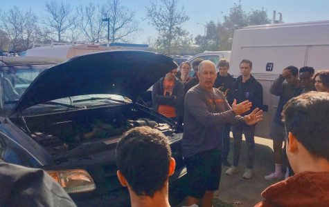 Students learn how to change a tire and jumpstart a car with health and PE teacher Pete Zell during their advisory block outside on Dec. 4.