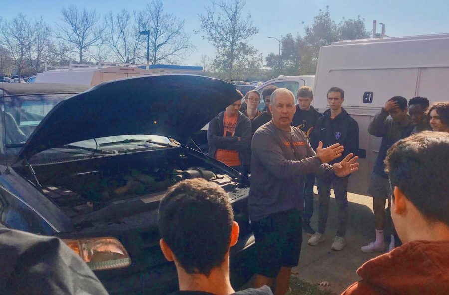 Students+learn+how+to+change+a+tire+and+jumpstart+a+car+with+health+and+PE+teacher+Pete+Zell+during+their+advisory+block+outside+on+Dec.+4.+