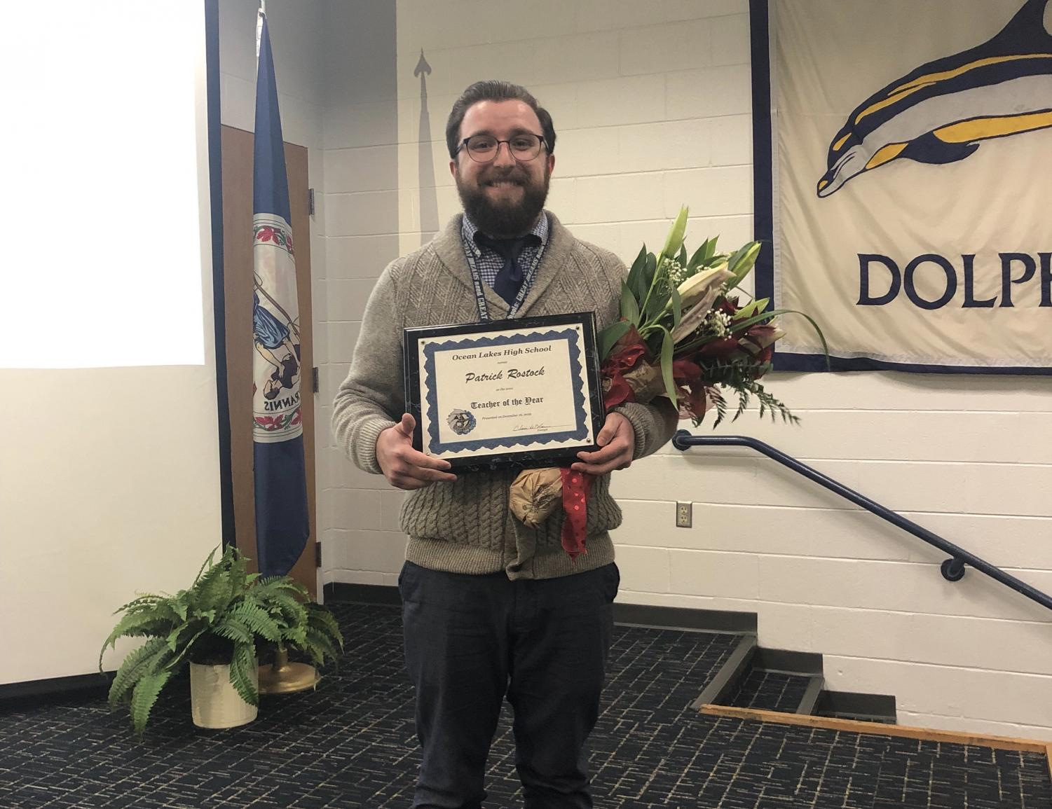 Patrick Rostock stands with his Teacher of the Year after the Distinguished Teacher Ceremony in the Schola on Dec. 16, 2019.