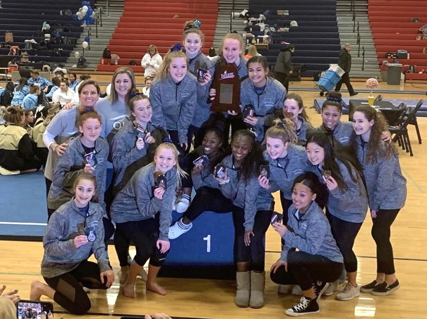 The+gymnastics+team+is+awarded+medals+after+their+state+title+win+at+Patriot+High+School+on+Feb.+21.