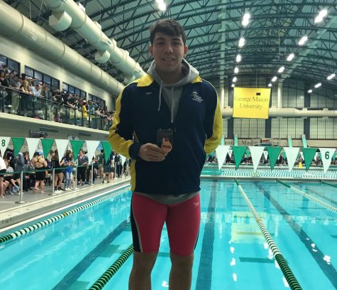 Kendall stands on the blocks at George Mason Aquatic Center with his second place state medal at the conclusion of the meet. Feb. 22.