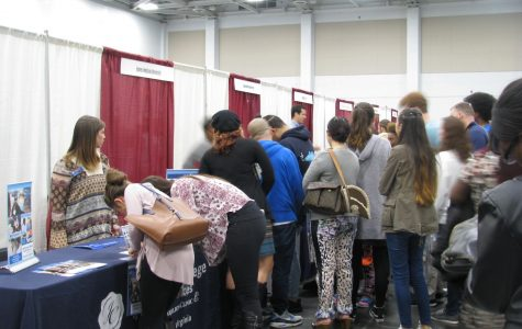 College and university representatives stand at their booths to hand out informative brochures and answer questions for prospective students at the Virginia Beach Convention Center.