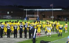 Each player of the football team stands facing the flag with their hands over their hearts during the National Anthem at the home game against Kellam on Oct. 9.