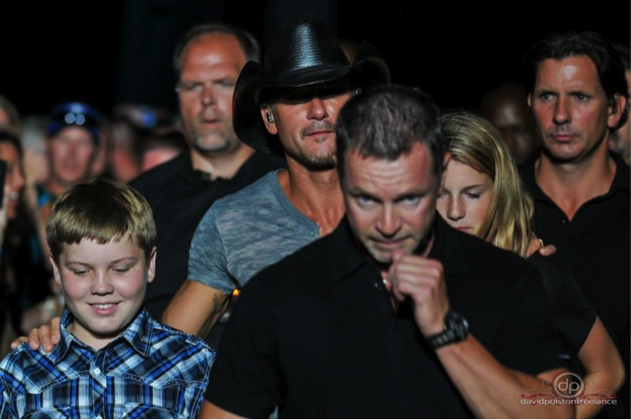 Photo of Mann walking behind Tim McGraw in June 2014 as they walk him to the stage at the Amphitheatre.