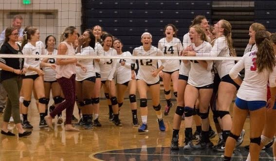 Girls' volleyball team embracing after their win against Kellam on Oct. 18, in the gym.  Photo by Jim Hart.