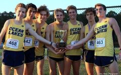 The cross country boys hold their Coastal Conference Championship trophy on October 26 at Kellam High School. Left to right sophomore Will Spollen, senior Sean Burtner, senior Dillon Schweers, junior Brent Bailey, junior Jacob Bushey, sophomore Tyler Lipps, and junior CJ Reed. Photo by Mary Ann Magnant.