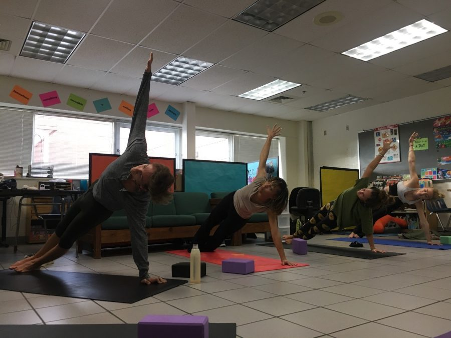 Yoga club members [left to right]: senior Christian Glover, teacher's assistant Jordan Freels, senior Adrienne Mclane, and senior Alexandria Phillips practice the side plank to increase strength at their meeting on January 18.