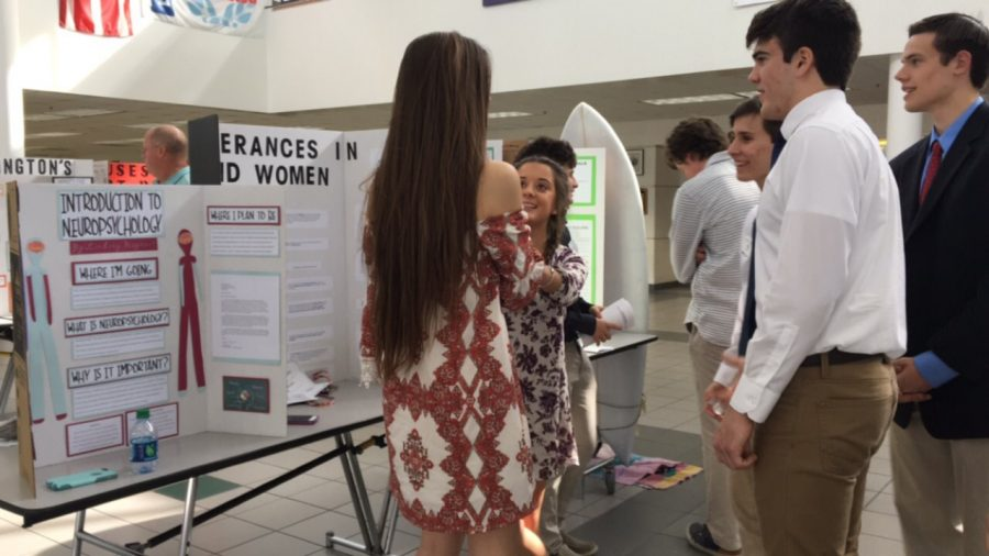 Math and Science Academy Junior Lindsay Magnant talks to friends Mady Ashworth and Jake Brown about her symposium research project Introduction to Neuropsychology at the symposium at Ocean Lakes High School on January 25.