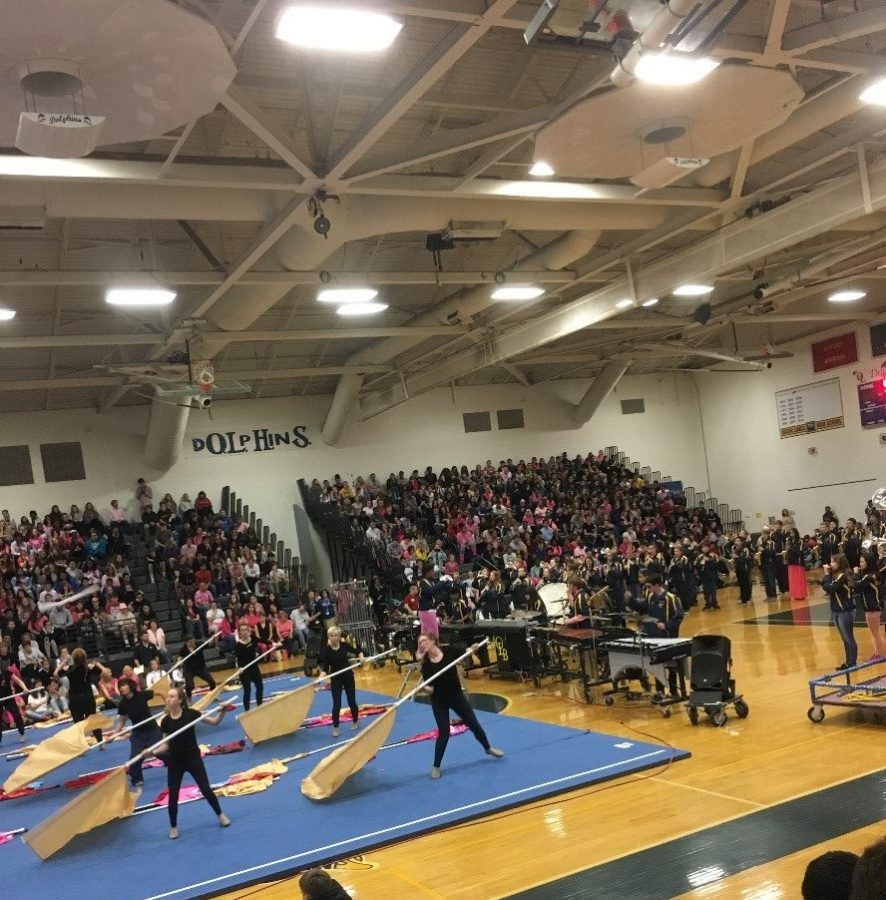 Depicts the band and color guard performing at the homecoming assembly. Taken by Makenna Miller