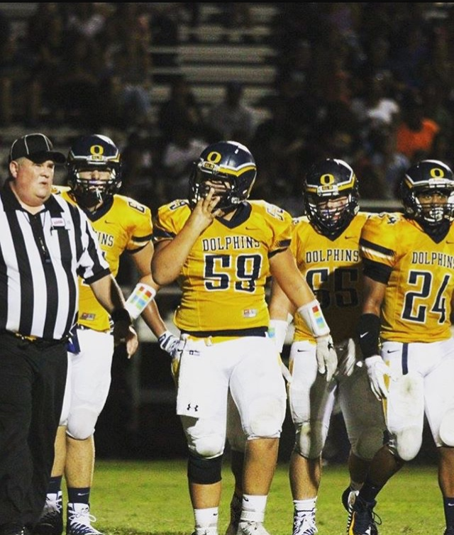 (Left to right) Sophomore Tyler Stephens, sophomore Nathan Brunelle, senior Joey Kirby, and senior Joshua Williams hustle off the field after a successful drive against Kellam on August 25. Photo credits: Redweaselmedia
