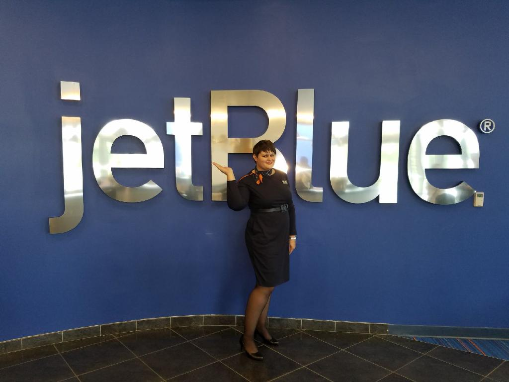Depicts Katrina Miller in her flight attendant attire standing near the   airline logo she works at. Photo by Makenna Miller