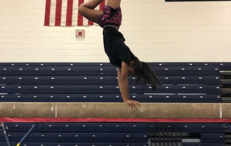 Senior Rutvi Patel performs a handstand on the balance beam in the Ocean Lakes gymnasium on Nov. 30, 2017.