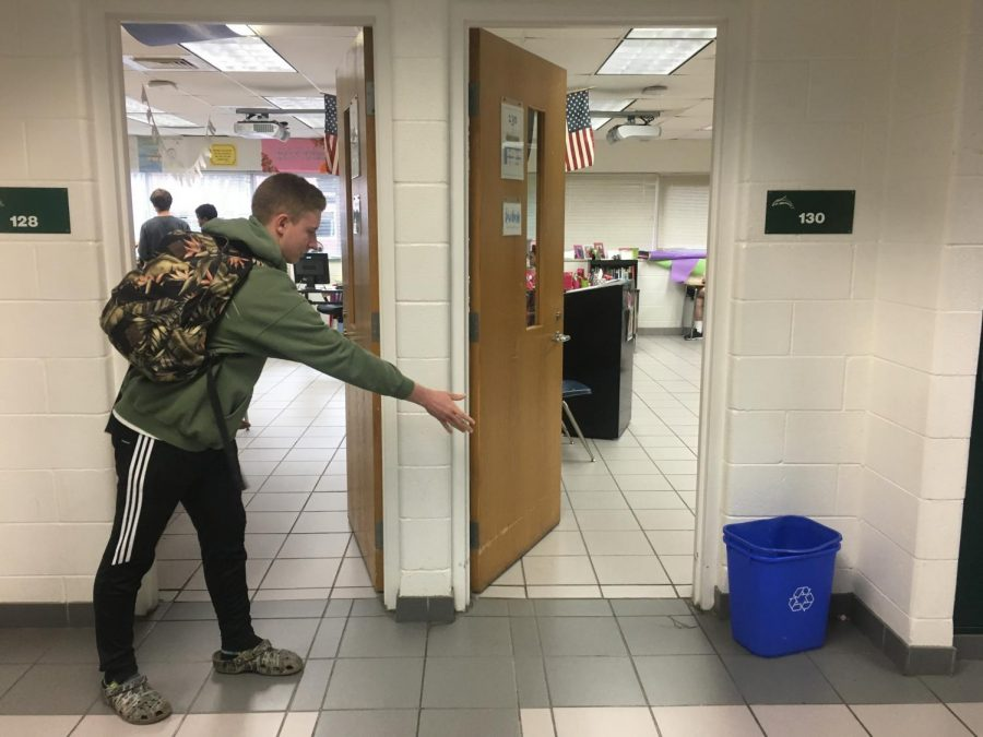Senior+Cody+Morris+throws+paper+into+the+recycling+bin+in+the+hallway.