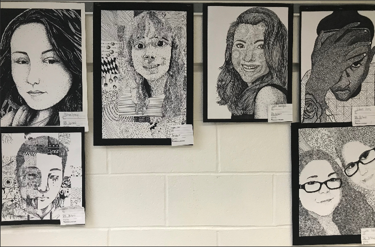 Self portraits hang on the wall outside the art room.