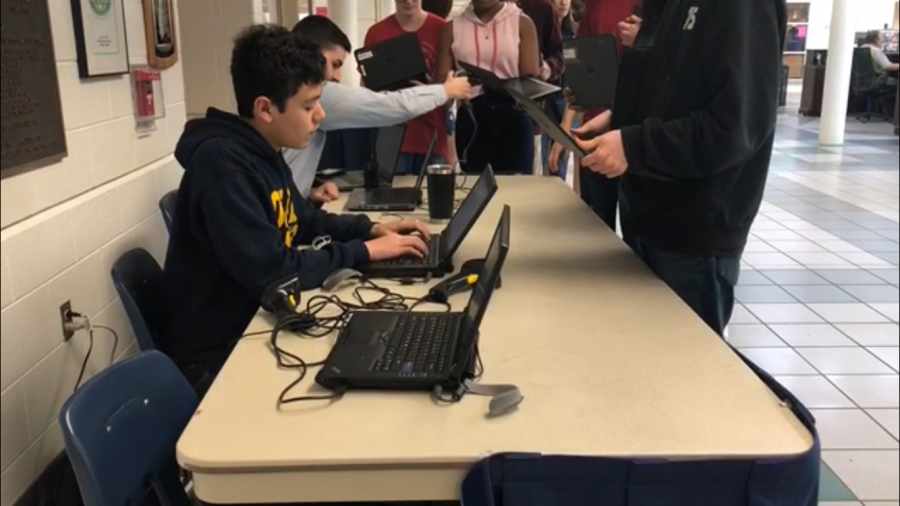 Student+Desk+Helper+Ethan+Schroeder+and+TST+Andres+Garrido+scan+the+chromebooks+of+freshmen.+Photo+taken+by+Abigail+Hicks.