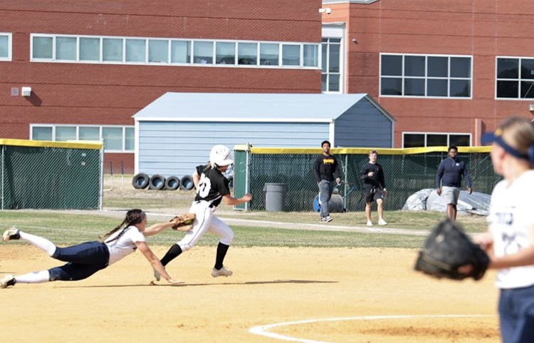 Senior Megan Munson dives to tag out a base runner thrown out by junior catcher Bailey Nelson to end the third inning.