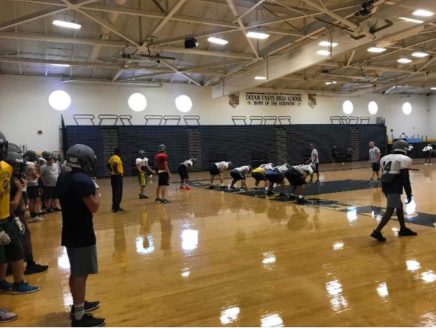 Dolphins football practice in the gym to prepare for their first game against Kellam at Kellam High School on Aug. 24.