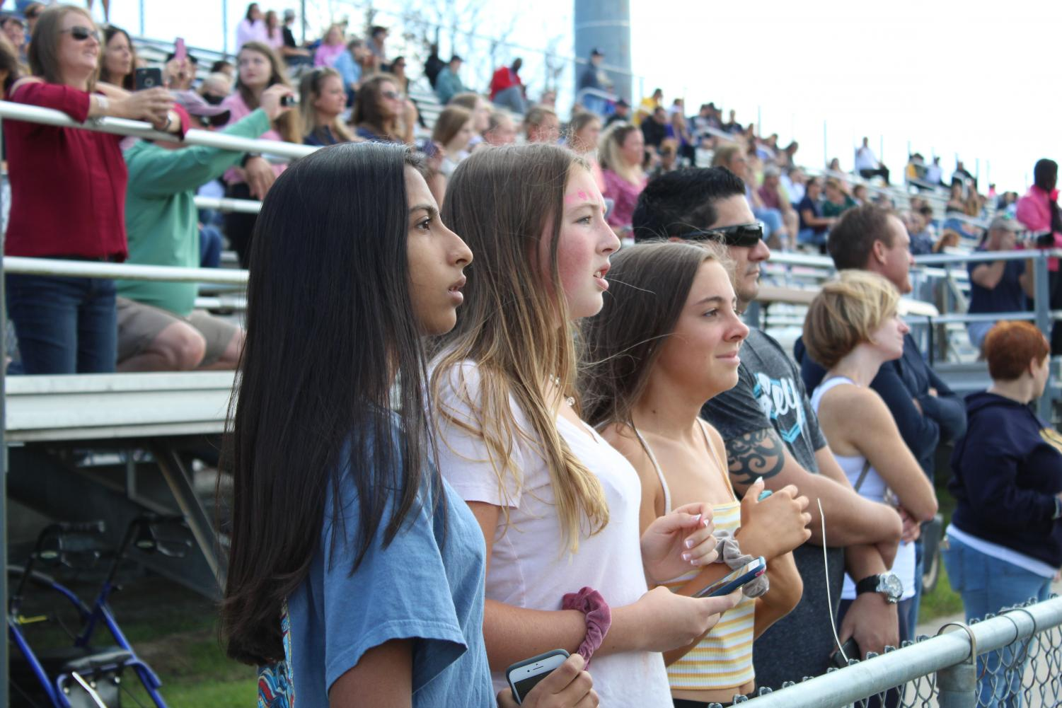 Sophomores (from left to right) Meher Mohann, Kristin Glasier, and Kelly McCarty attentively watch the Homecoming game on Oct. 13.
