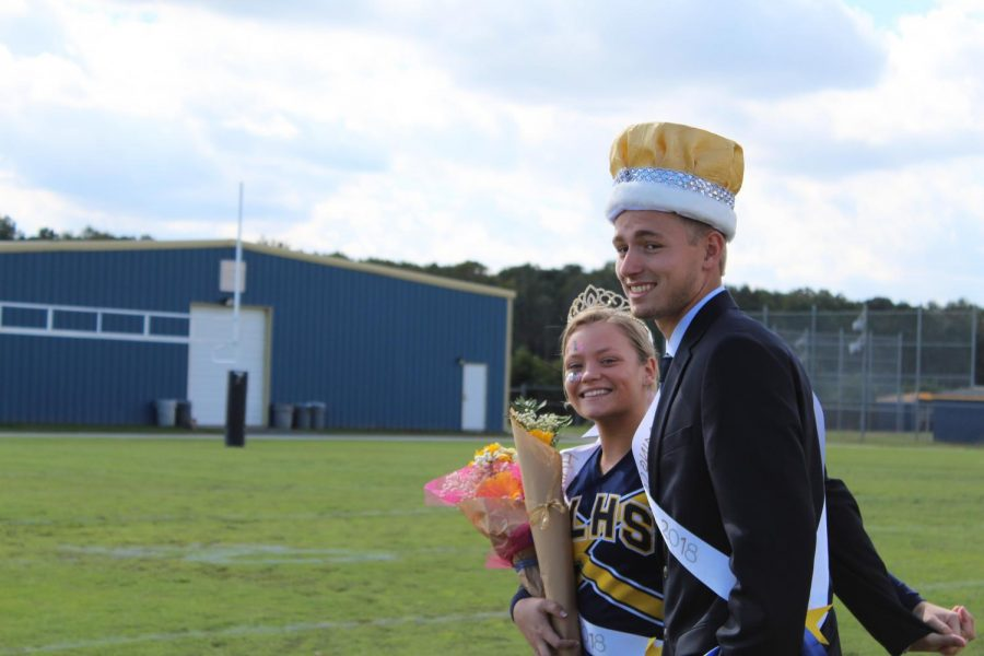 Seniors Madison Coleman and Nick Vogel, this year's homecoming queen and king, smile for the camera as they enjoy recent announcement, crowned by principal Claire LeBlanc.