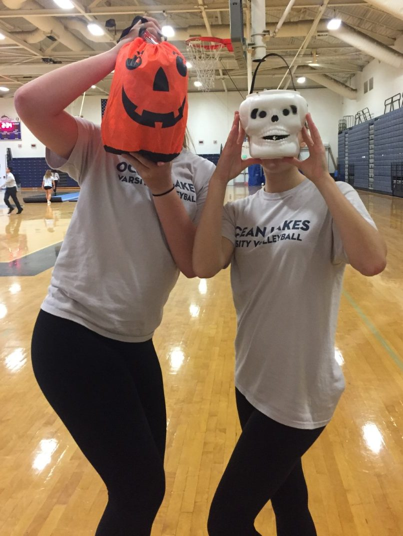 Hannah Donaldson and Maddy Delmonte play with their spooky goody bags given to them by teammates before their volleyball game against First Colonial.