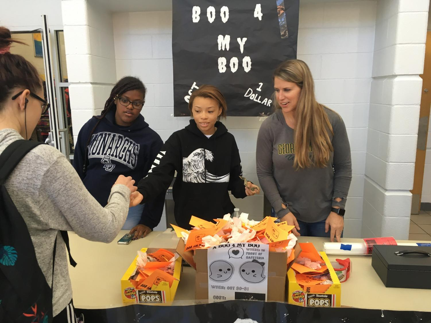 AVID students and coordinator Michelle McAfee sold decorated Tootsie Pops to students outside the cafeteria for $1 each. Oct. 30, 2018.