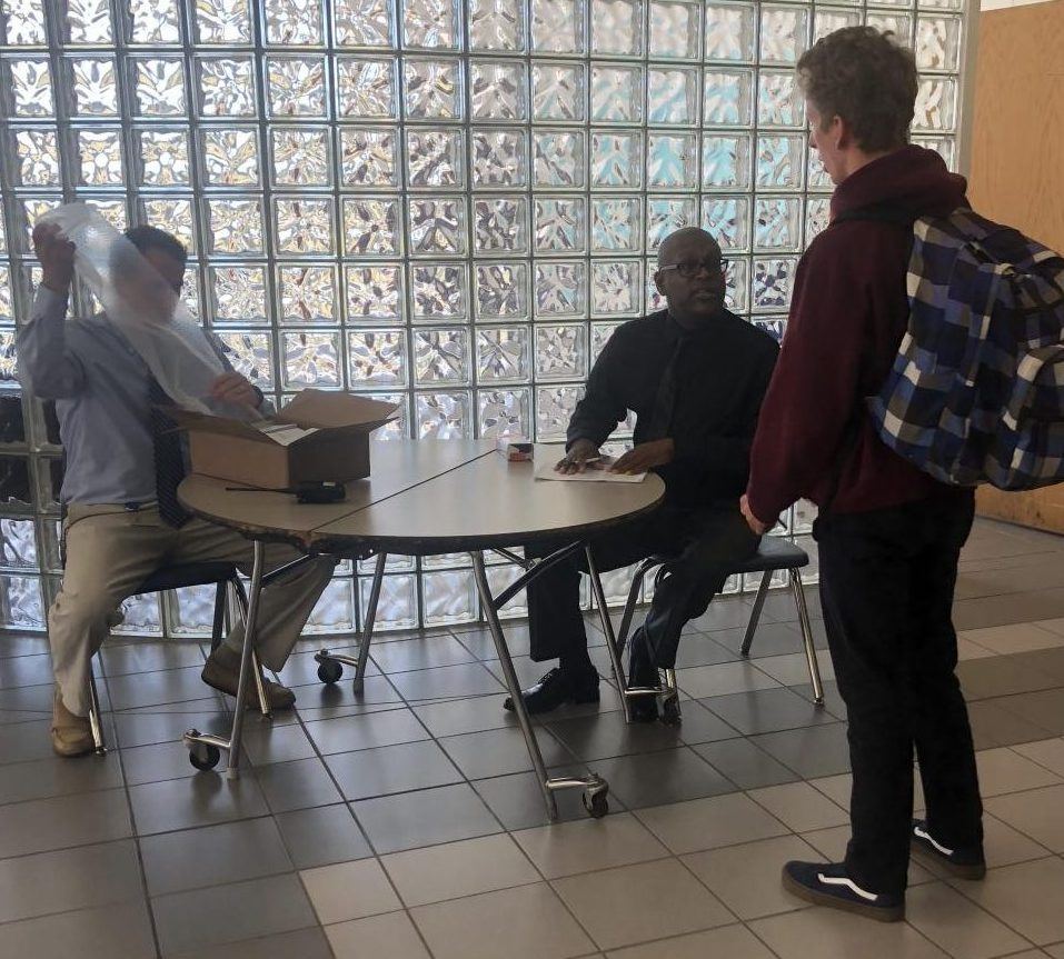 MSA Coordinator and Counselor Bryan Everett prepare to pay senior Joseph Mastrullo on Oct. 31 in the cafeteria.