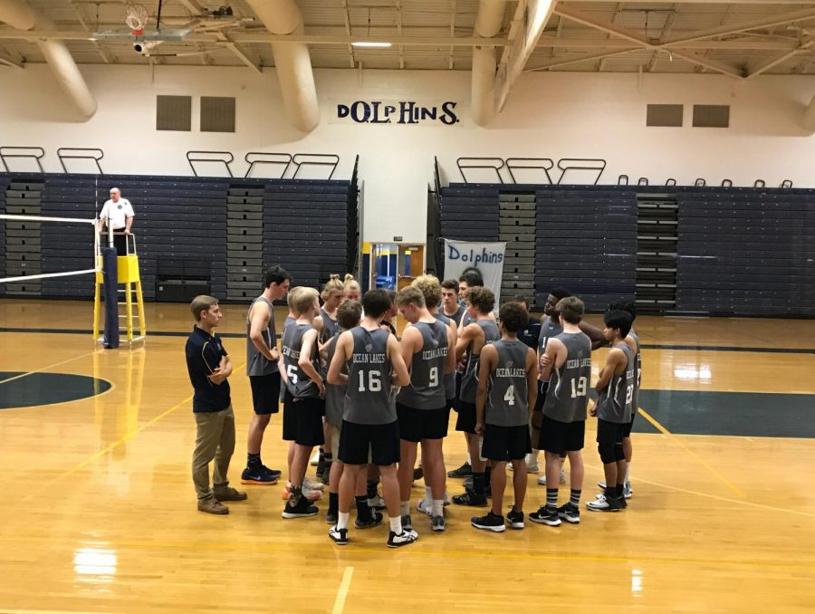 Ocean Lakes boys volleyball rallies around coach Boomer during a home game.