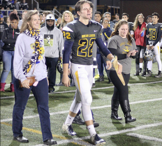Xander Jedlick walks with his family on the Kellam football field for the Dolphins senior night on Nov. 9.
