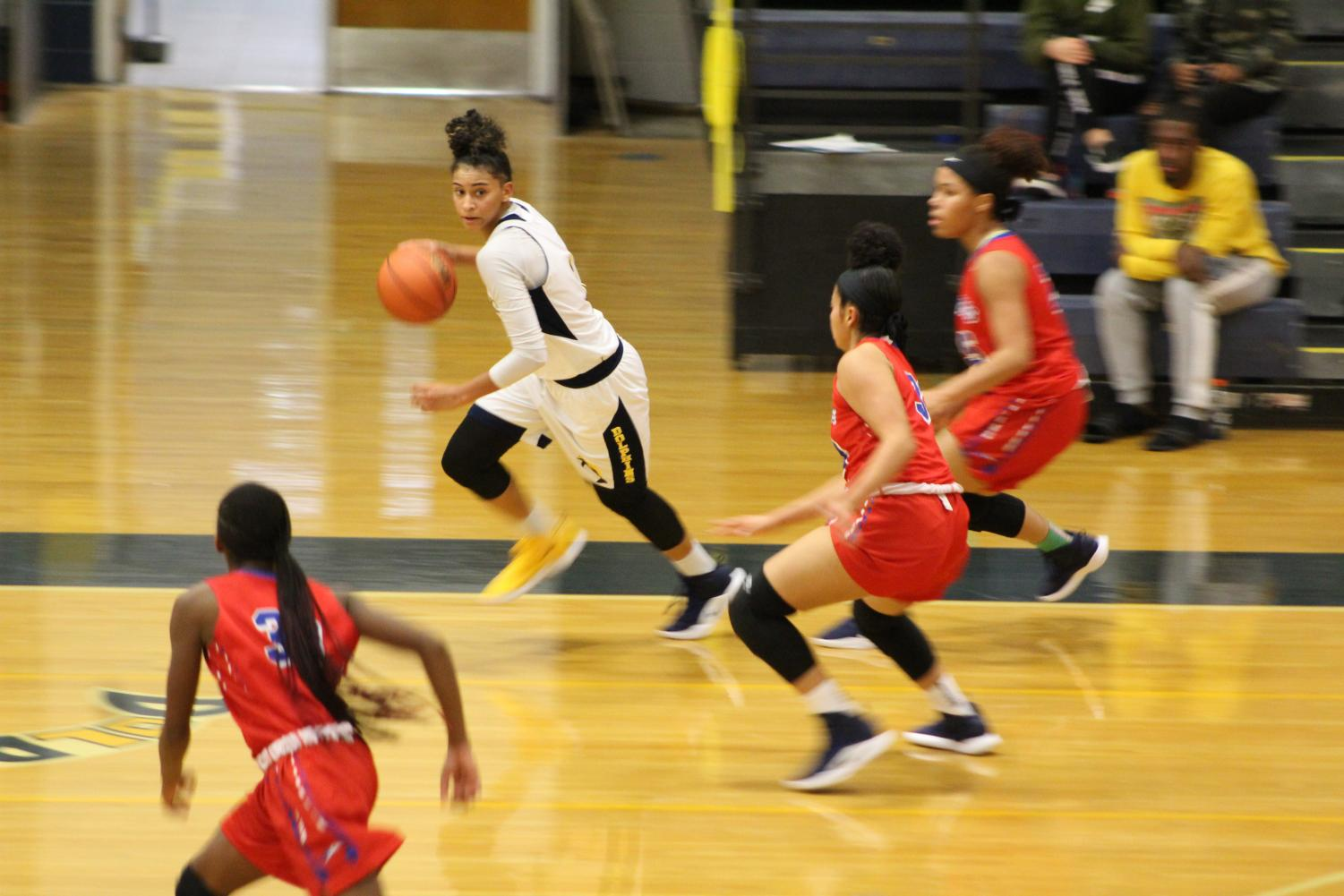 Senior Kyla McMakin dribbles the ball down the court during the teams' game against Princess Anne on Nov. 30.