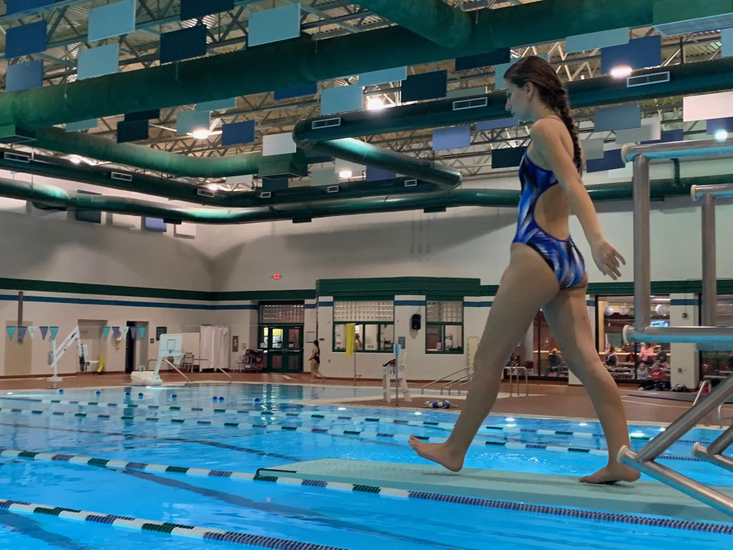 Senior captain Rachelle Jacob walks to the end of the board to start a back dive at Princess Anne Recreation Center on Nov. 19.