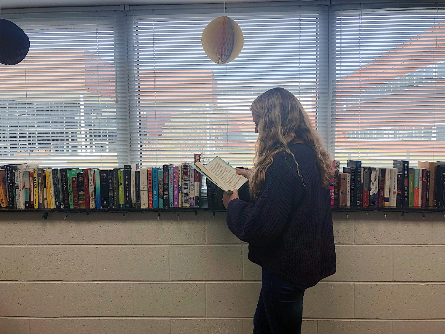 Junior Isabelle Weiss checks out a copy of Frat Girl, by Kiley Roache, during her fourth block English class. Photo by Katie Kerrigan.