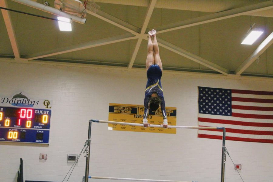 Freshman Rebekkah Funderburk holds herself up on the parallel bars at the gymnastics meet Monday, Jan. 7.