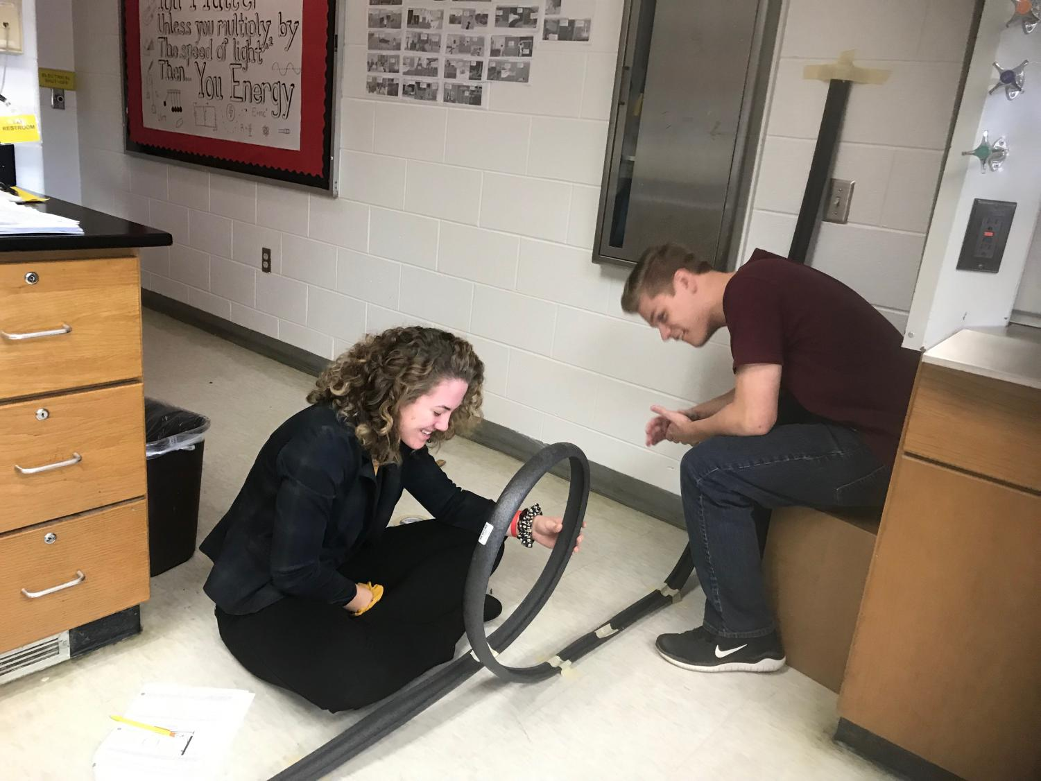 Senior Kay Brennan and junior Dylan Young make their DIY roller coaster in Linda Spangler's 2B physics class on Friday, Jan. 11.