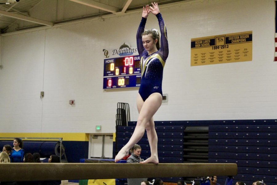 Junior Anna Harmon starting off her balance beam routine, Monday, Jan. 7.