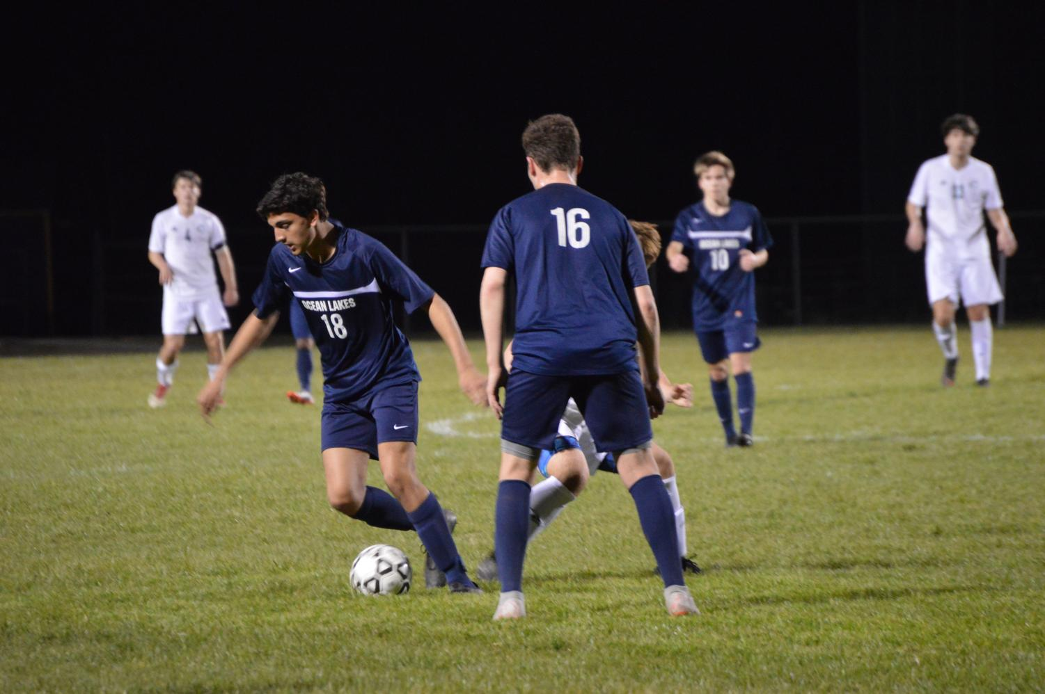 Mid-fielder Matthew Harris dribbles the ball against Cox while senior, defender Dawson Weiss and mid-fielder Troy Daigneau looks on.