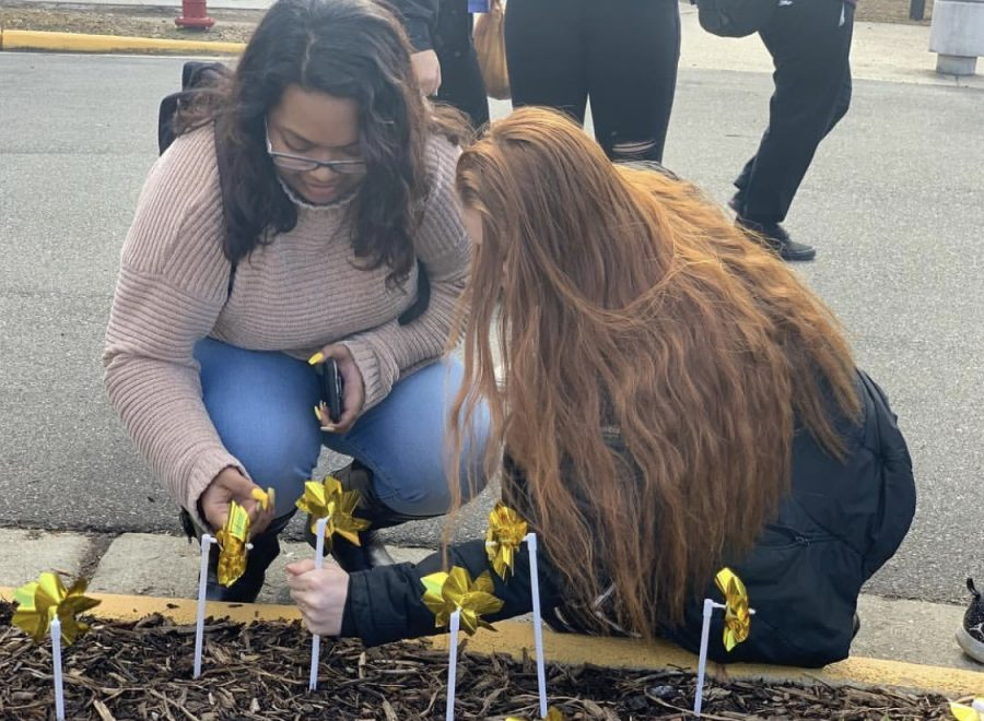 Seniors Anis Mohammad and Hannah Morfeld place their legacy pinwheels in the ground during advisory on Wednesday, March 6.