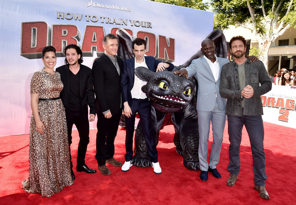 Depicts Gerard Butler, Djimon Hounsou, Jay Baruchel, America Ferrera, Craig Ferguson, Kit Harington standing around a model of the dragon Toothless. Picture source from Zimbio.com.