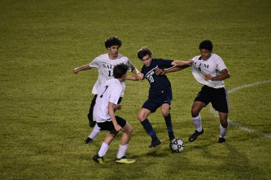 Junior Troy Daigneau keeps the ball away from three Salem players on April 25, 2019 at Ocean Lakes High School.