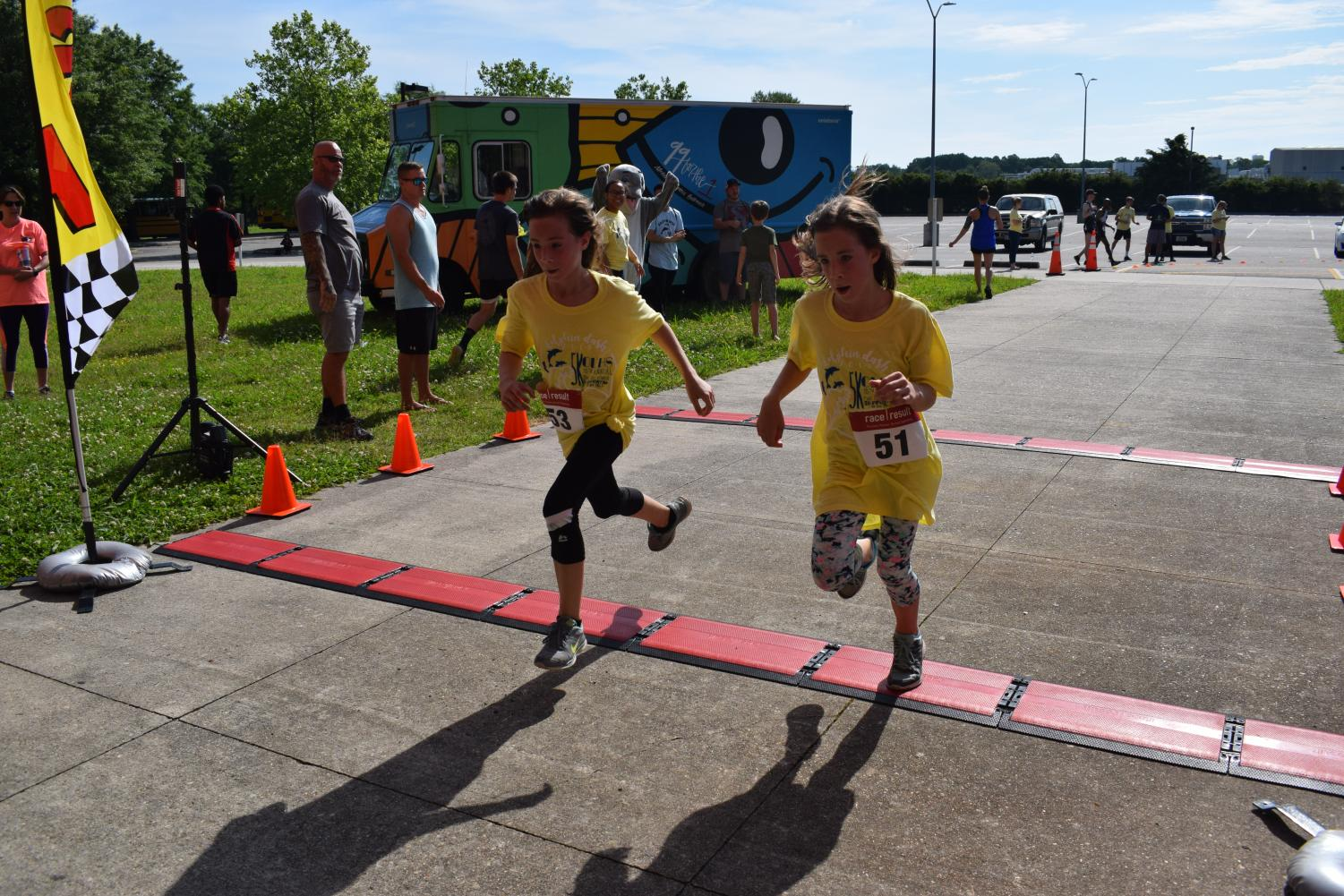 English teacher Jessica Scheible's twin daughters, Lucy and Brianna, cross the finish line and head to gym for after race festivities.